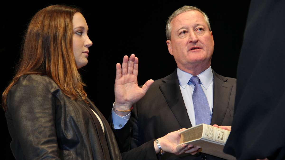 Jim Kenney is sworn in as Philadelphia's 99th mayor at the Academy of Music while his daughter, Nora, holds the Bible. (Emma Lee/WHYY)