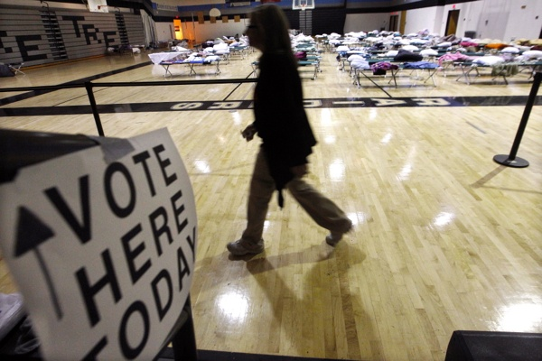 <p><p>A person walks through a makeshift shelter in a gymnasium at Toms River East High School as they arrive to vote Tuesday, Nov. 6, 2012, in Toms River, N.J. (AP Photo/Mel Evans)</p></p>