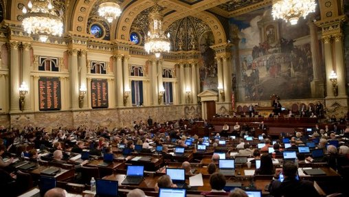 Facing forward from the rear, arched ceilings, painted murals, and members of the Pa. legislature seated at desks