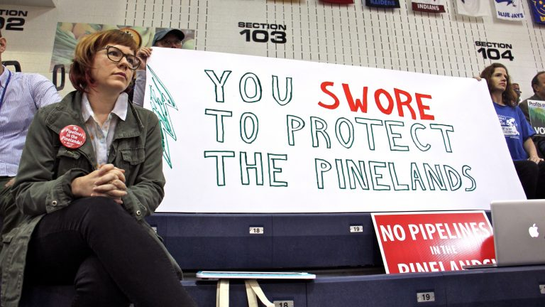 Protesters armed with signs fill the bleachers at Pine Belt Arena in Toms River, where the New Jersey Pinelands Commission held a public hearing on the Southern Reliability pipeline through Burlington and Ocean counties. (Emma Lee/WHYY, file)