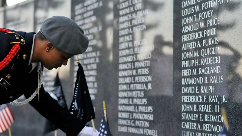 POW/MIA flags are placed near the names of ten soldiers missing in action during a ceremony at the Vietnam Veterans Memorial in Philadelphia.