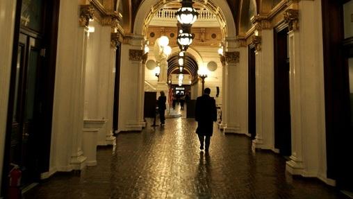 A man walks down a hall toward the light of the Capitol rotunda