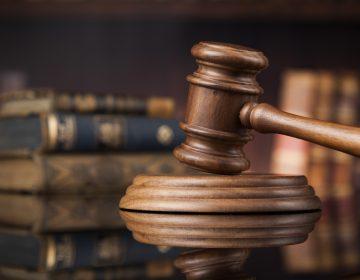 Court gavel, brown wood against a dark background