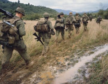 Soldiers are walking through a muddy field in Vietnam on a search and destroy operation