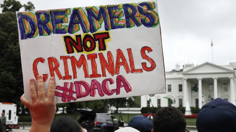 FILE- In this Aug. 15, 2017, file photo, a woman holds up a signs in support of the Obama administration program known as Deferred Action for Childhood Arrivals, or DACA, during an immigration reform rally at the White House in Washington. (AP Photo/Jacquelyn Martin, File)