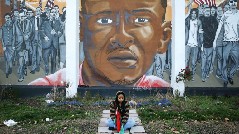 In a Dec. 16, 2015 file photo, Jazmin Holloway sits below a mural depicting Freddie Gray at the intersection of his arrest, in Baltimore. (Patrick Semansky/AP Photo, File)