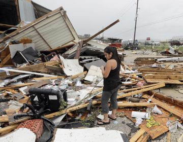 Jennifer Bryant looks over the debris from her family business destroyed by Hurricane Harvey Saturday, smashing homes and businesses and lashing the shore with wind and rain so intense that drivers were forced off the road because they could not see in front of them. (David J. Phillip/AP Photo)