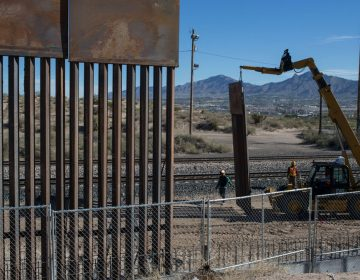 In this March 30, 2017 file photo, Workers use a crane to lift a segment of a new fence into place on the U.S. side of the border with Mexico. (AP Photo/Rodrigo Abd)