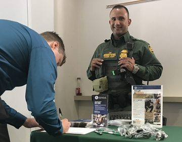 Border Patrol Agent Lanllony Molina of Erie, Pennsylvania, smiles as a job-seeker gives his information during an employment fair Thursday at Temple University. (Laura Benshoff/WHYY)