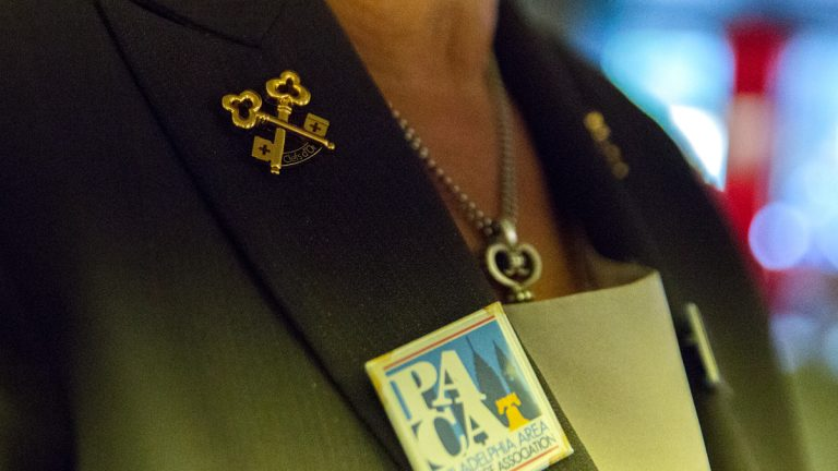 Fran Nachman wears crossed gold keys on her lapel, a symbol of her membership to Les Clefs d'Or, an international organization of professional hotel concierges. (Lindsay Lazarski/WHYY)