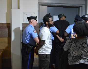 Two of the protesters are put on a freight elevator at City Hall after being removed from Council chambers. (Tom MacDonald/WHYY)