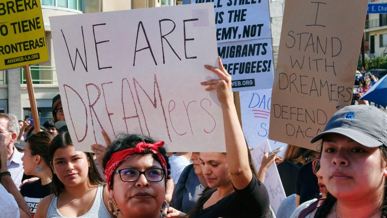 Supporters of the Deferred Action for Childhood Arrivals, or DACA chant slogans and hold signs while joining a Labor Day rally in downtown Los Angeles on Monday, Sept. 4, 2017.