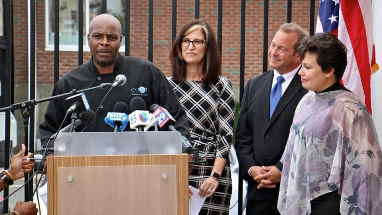 Mark Woodall (left), a former state prison inmate and current chef at Cathedral Kitchen, talks about the difficulty of finding permanent shelter during re-entry. With him are (from right) Camden County Freeholder Carmen Rodriguez, Freeholder Director Louis Cappelli Jr., and Volunteers of America Chief Operating Officer Pat McKernan, who announced a new plan to end homelessness. (Emma Lee/WHYY)