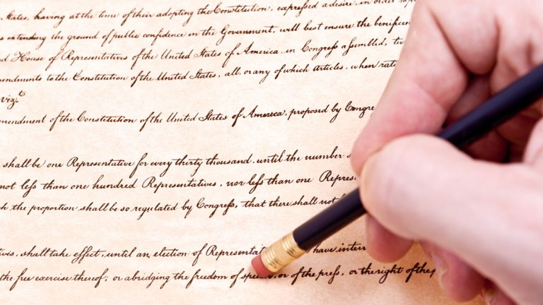(<a href='https://www.bigstockphoto.com/image-24731483/stock-photo-closeup-of-hand-pencil-erasing-first-amendment-to-u-s-constitution'>Qingwa</a>/Big Stock Photo)