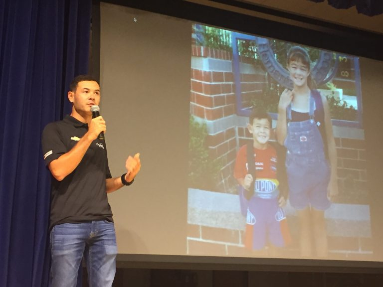 Top NASCAR racer Kyle Larson addresses students Tuesday at t St. Georges Technical High School while a photo with his sister from his youthful racing days is projected on a screen. (Cris Barrish/WHYY)