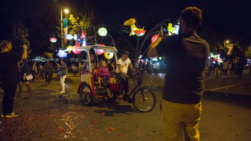 A family takes a portrait on a pedicab at the opening of ''Fireflies'' on the Ben Franklin Parkway. (Emily Cohen for NewsWorks)