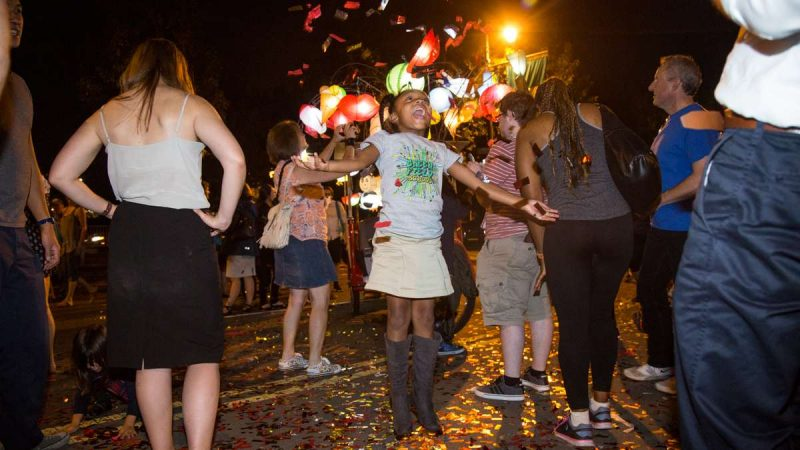 Nia Adams, 6, plays with the confetti after the debut of ''Cai Guo-Qiang: Fireflies'' on the Ben Franklin Parkway in Philadelphia September 14th 2017. (Emily Cohen for NewsWorks)