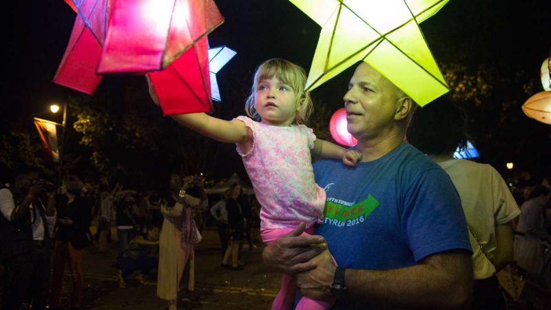 Bridget Corrigan, 3, is held up by her father, Jim, for a closer look at the lanterns after their debut in ''Cai Guo-Qiang: Fireflies'' on the Ben Franklin Parkway in Philadelphia September 14th 2017. (Emily Cohen for NewsWorks)