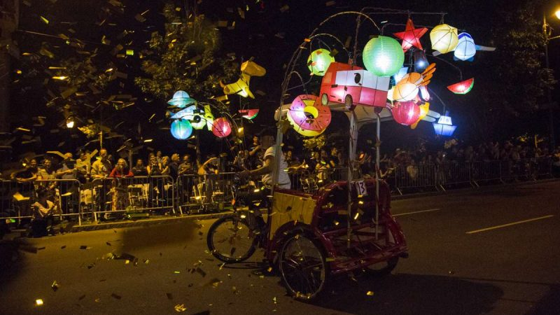 Confetti flies as a pedicab performs in the debut of ''Cai Guo-Qiang: Fireflies'' on the Ben Franklin Parkway. (Emily Cohen for NewsWorks)