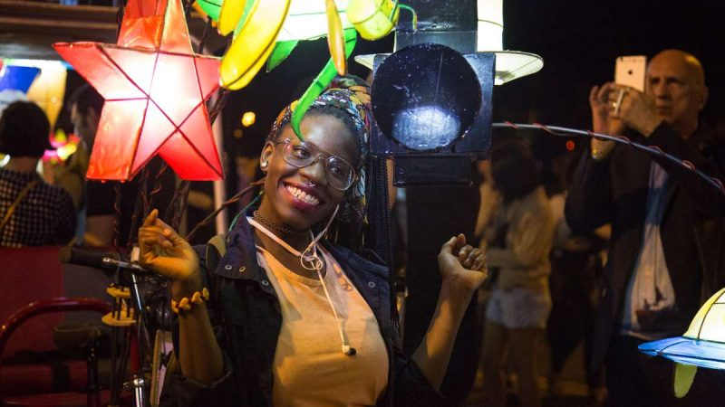 Eve Kabah poses for a photo with the lanterns after the debut of ''Cai Guo-Qiang: Fireflies'' on the Ben Franklin Parkway in Philadelphia. (Emily Cohen for NewsWorks)