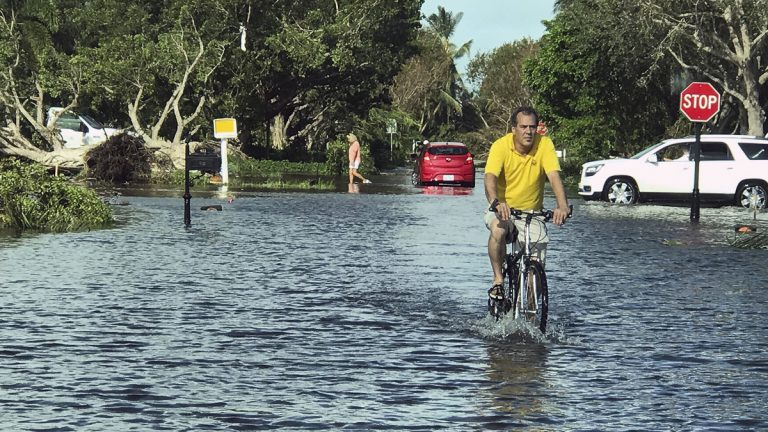 A man rides through storm water in Naples, Fla., in the aftermath of Hurricane Irma, Monday, Sept. 11, 2017. Florida Gov. Rick Scott says there's damage across the state caused by Hurricane Irma and it's still too dangerous for residents to go outside or return from evacuation. (AP Photo/Robert Ray)