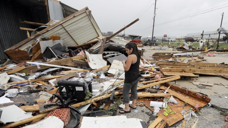 Jennifer Bryant looks over the debris from her family business destroyed by Hurricane Harvey Saturday, Aug. 26, 2017, in Katy, Texas. Harvey rolled over the Texas Gulf Coast on Saturday, smashing homes and businesses and lashing the shore with wind and rain so intense that drivers were forced off the road because they could not see in front of them. (AP Photo/David J. Phillip)