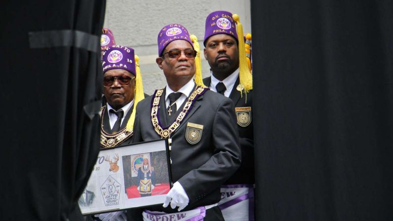 Members of the Octavius V. Catto African-American Elks Lodge await the unveiling of the monument wearing purple hats with yellow tassles