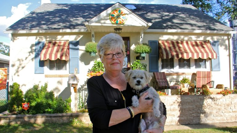 A woman with white hair stands in front of her yellow house, holding her white haired dog