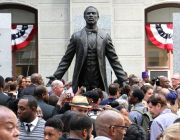 A statue of Octavius Catto at it's unveilling - statue facing front with arms spread open and back, people in the foreground in Philadelphia