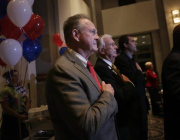 Former Alabama Chief Justice and U.S. Senate candidate Roy Moore, stops to say the Pledge of Allegiance as he walks around greeting supporters before his election party, Tuesday, Sept. 26, 2017, in Montgomery, Ala.