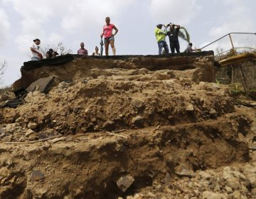 Residents Wednesday look over the edge of a bridge that was swept away by Hurricane Maria