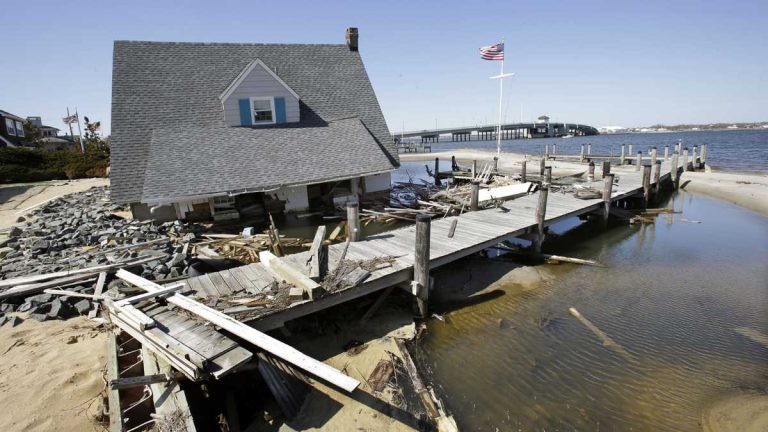 A home rests next to a pier in Barnegat Bay in 2013 near the Mantoloking Bridge in Mantoloking, N.J., after it was swept away by Superstorm Sandy. (Mel Evans/AP Photo)