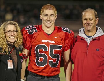 This Oct. 31, 2014, photo provided by Patrick Carns shows Timothy Piazza, (center), with his parents Evelyn and James Piazza, during Hunterdon Central Regional High School football's 'Senior Night' at the high school's stadium in Flemington, N.J. (Patrick Carns via AP)