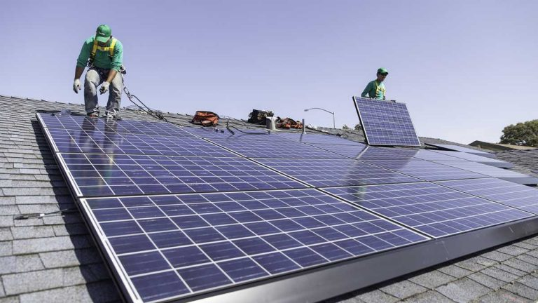 In this undated photo provided by SolarCity, workers install solar panels on the roof of a home. (SolarCity/AP Photo)