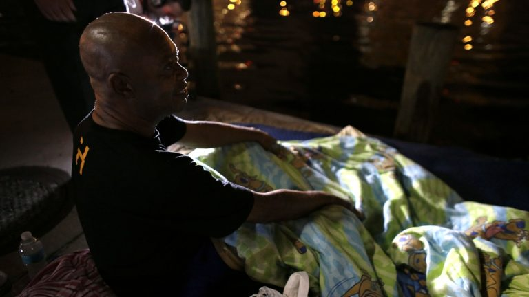 Homeless veteran James Thomas, 62, who was sleeping along the Miami River, talks with officials from the Veteran's Administration during the Point In Time Homeless Census, Thursday, Jan. 22, 2015, in Miami.