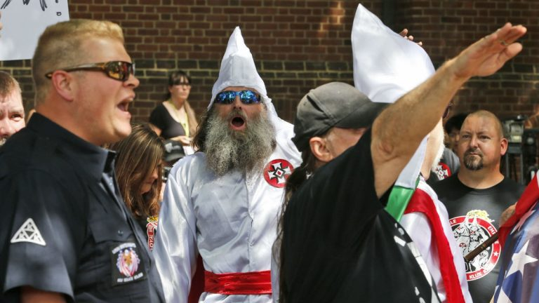 Members of the KKK are escorted by police past a large group of protesters during a KKK rally Saturday, July 8, 2017, in Charlottesville, Va. A month later, as white supremacists protested the proposed removal of a Confederate monument, counter-protester Heather Heyer was killed when James Alex Fields drove a speeding car into the crowd. (AP Photo/Steve Helber)