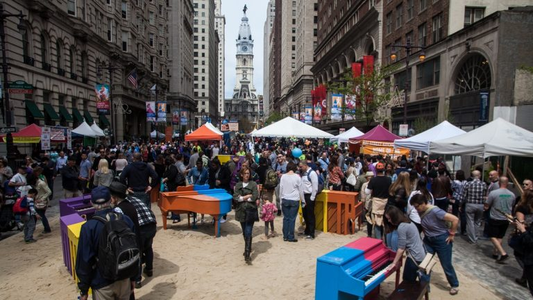 People and vendors tents set upon beach sand on Broad Street with City Hall in the background