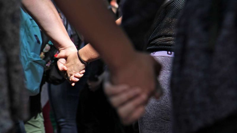 Students hold hands during a memorial service for slain Temple student Jenna Burleigh, held in the sun-dappled Founder's Garden on campus.