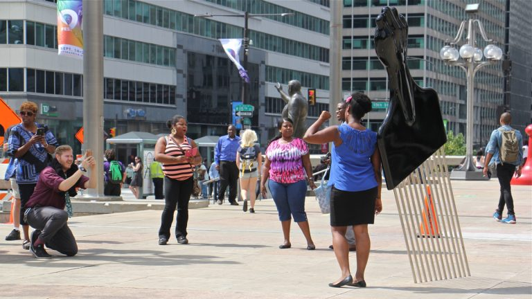Frank Rizzo's statue  on the plaza of the Municipal Services Building stands at the center of controversy. Recently this afro pick with a black power symbol was added.(Emma Lee/WHYY)