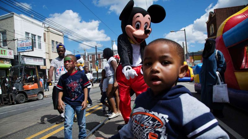 A young man dressed as Mickey Mouse plays with neighborhood children on Woodland Avenue. (Annie Risemberg for NewsWorks)