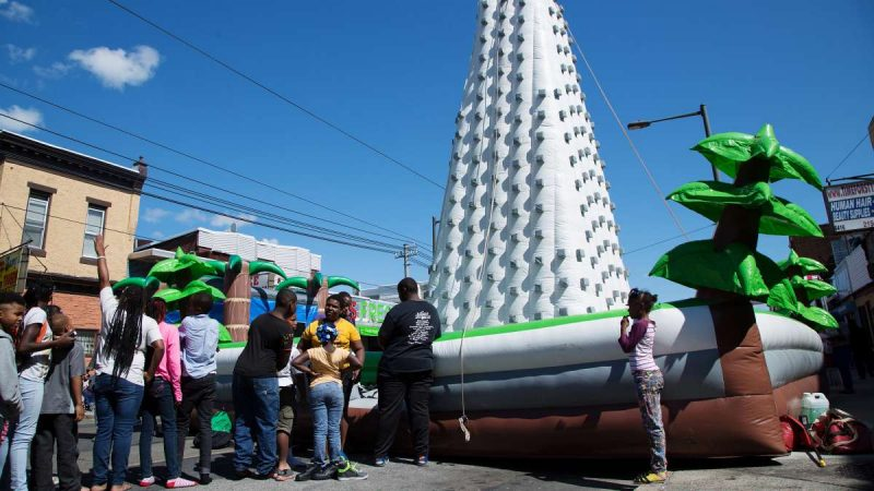 Children wait in line to attempt to reach the top of an inflatable rock-climbing wall during Southwest Pride Day festivities in Southwest Philadelphia. (Annie Risemberg for NewsWorks)