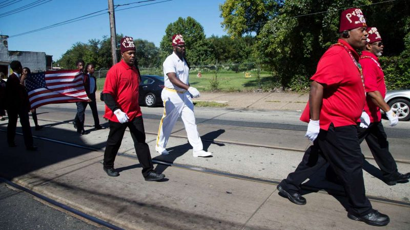 Members of the Pyramid Temple #1, the Prince Hall Shriners of Philadelphia, walk down Woodland Avenue at the start of the Southwest Pride Day parade. The Shriners are a fraternity best known for administering the Shriners Hospital for Children. (Annie Risemberg for NewsWorks)