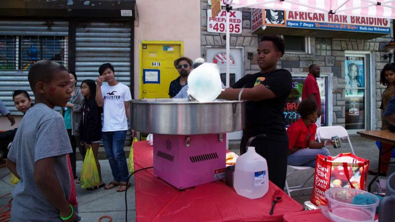 A street vendor spins cotton candy for waiting customers. (Annie Risemberg for NewsWorks)