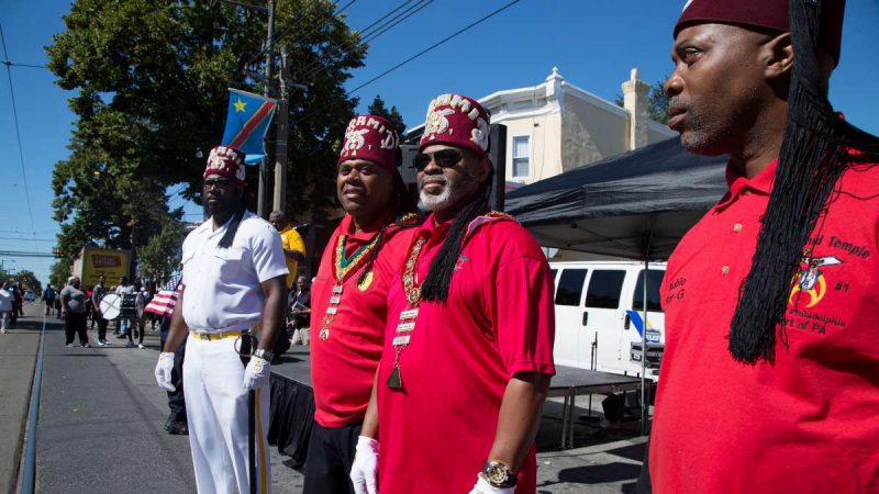 Members of the Pyramid Temple #1 look on as residents participate in Southwest Pride Day festivities on Woodland Avenue. (Annie Risemberg for NewsWorks)