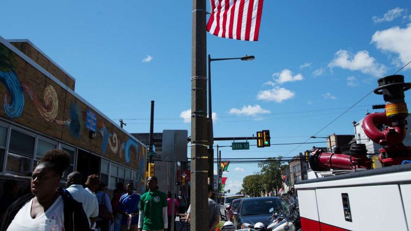 The American flag hangs on 65th Street and Woodland Avenue in line with flags of various Caribbean and African nations. (Annie Risemberg for NewsWorks)