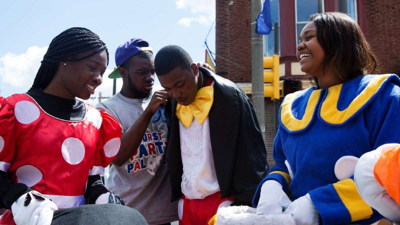 A group dressed in Disney character costumes prepare to go into the crowd. (Annie Risemberg for NewsWorks)