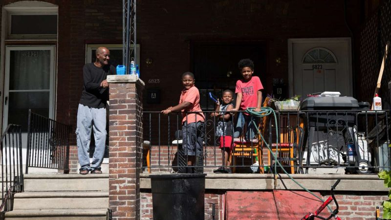 A family watches the Southwest Pride Day parade from their porch on Woodland Avenue. (Annie Risemberg for NewsWorks)