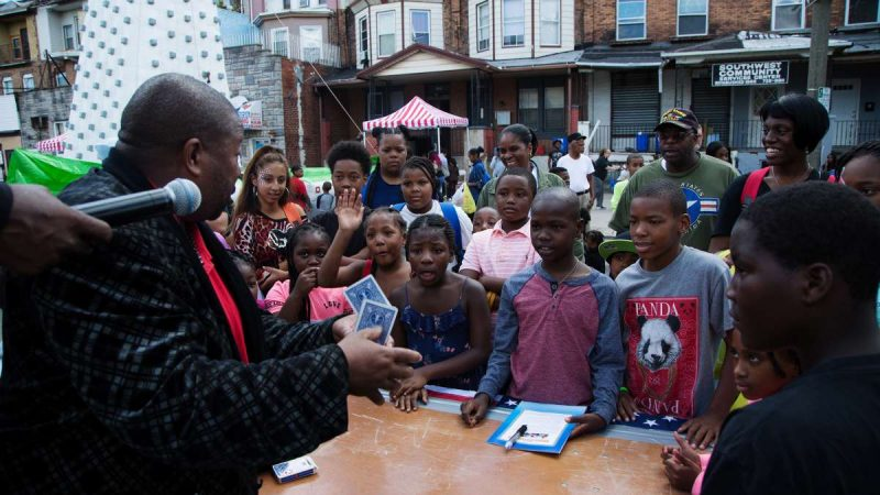 Children look on in awe as a magician completes a card trick in front of them. (Annie Risemberg for NewsWorks)
