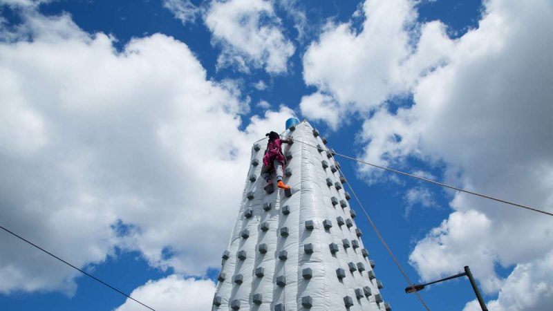 A girl approaches the top of an inflatable rock-climbing wall on Woodland Avenue. (Annie Risemberg for NewsWorks)