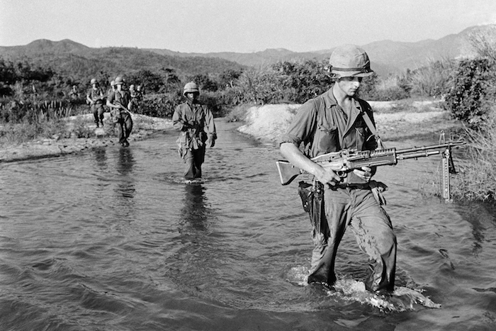 U.S. Marines walking through the stream during a patrol 15 miles southwest of Da Nang airbase in Vietnam on Thursday, May 20, 1965, in a newly assigned territory to the American Marines. (AP Photo/John T. Wheeler)